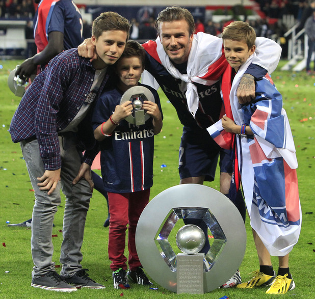 David Beckham and his sons pose with the cup.