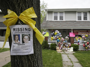 A missing poster rests on a tree outside the home of Amanda Berry
