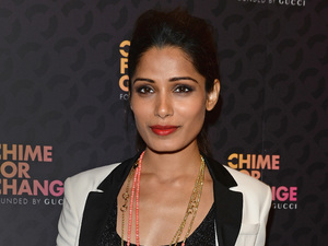 "Actress Freida Pinto arrives at the Royal Box photo wall ahead of the ""Chime For Change: The Sound Of Change Live"""
