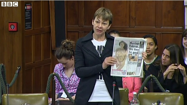 Caroline Lucas covers up to brandish 'The Sun'
