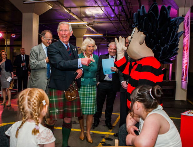 The Prince of Wales with the Duchess of Cornwall and Dennis the Menace during their visit for the official opening of DC Thomson Printing Plant in Dundee.