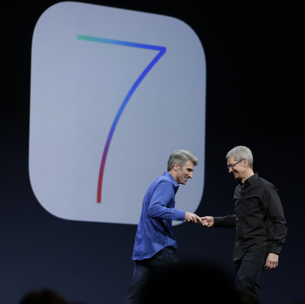 Craig Federighi, senior vice president of software engineering at Apple, left, greets Apple CEO Tim Cook after the introduction of iOS 7 during the keynote address of the Apple Worldwide Developers Conference