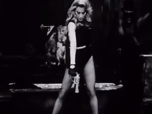The singer brandishes a gun in the new black and white clip.