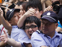 Bystanders are left bloodied after a crowd surge during Beckham's visit to China.
