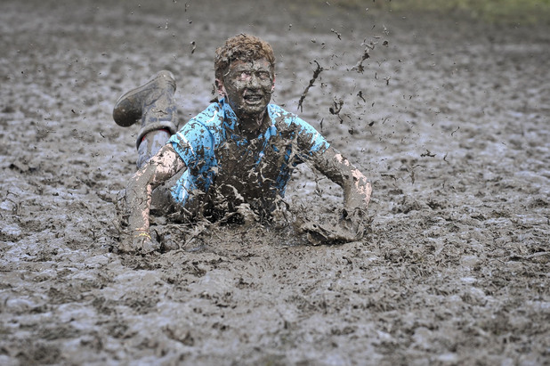 Tom Wilder, 17, from Kent, gets into the festival spirit and performs a dramatic slide in the Glastonbury Festival mud during the event held on Worthy Farm, Pilton.