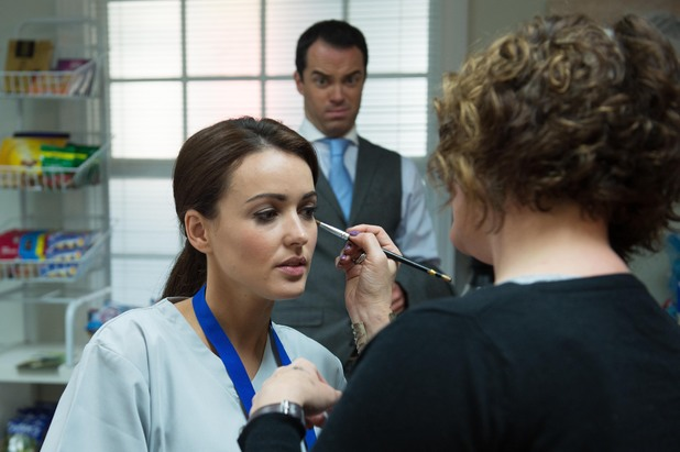 Joseph Thompson watches Karen Hassan have her make-up applied