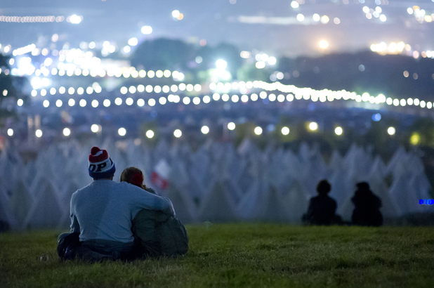 Festival goers wait for the sun to rise at Glastonbury Festival, at Worthy farm in Somerset.
