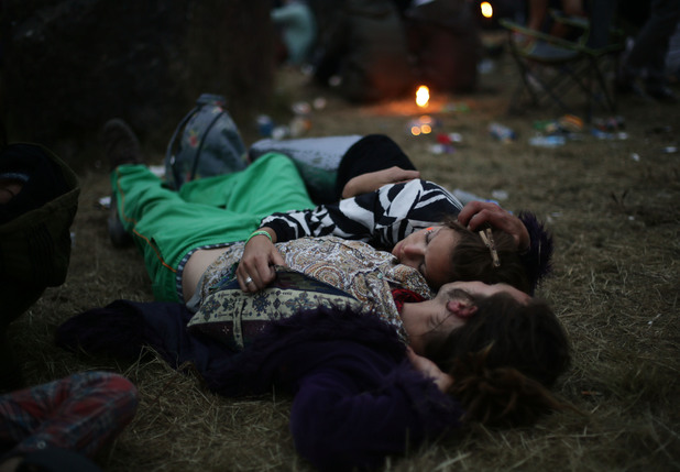 Festival-goers sleeping as the sun comes up on Sunday morning