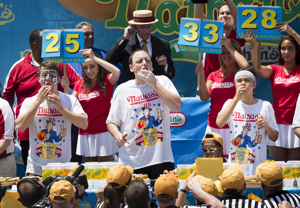 Tim Janus, Joey Chestnut, and Matt Stonie compete in the Nathan's Famous Fourth of July International Hot Dog Eating contest at Coney Island, Thursday, July 4, 2013