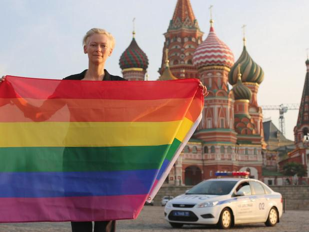 Tilda Swinton with a rainbow flag in front of Saint Basil's Cathedral near the Kremlin