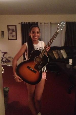 Julie Fermin poses with the guitar John Mayer bought her
