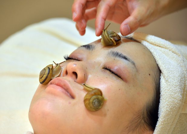 Snails crawls on the face of a woman for the demonstration of a new beauty treatment at the beauty salon