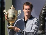 Wimbledon Mens Champion Andy Murray with his winner's trophy in front of the Fred Perry statue at Wimbledon