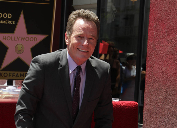 Bryan Cranston sits with his star at his Hollywood Walk of Fame induction ceremony