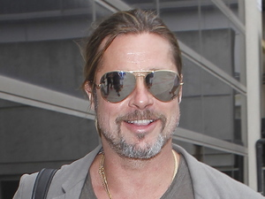 Brad Pitt arrives at LAX airport pulling his own suitcase