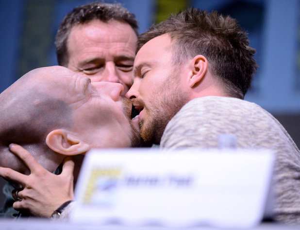 Actor Bryan Cranston watches actor Aaron Paul kiss a Walter White face mask onstage at the 'Breaking Bad' panel during Comic-Con International 2013 at San Diego Convention Center on July 21, 2013 in San Diego, California