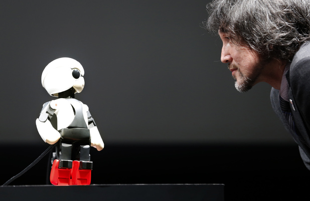Kirobo, the world's first talking robot, 'talks' to Toyota Motor Corp project general manager Fuminori Kataoka at a press conference in June 2013