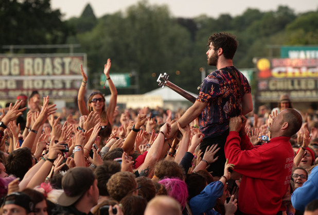 Yannis Philippakis climbs the barrier during Foals' set at Reading 2013.