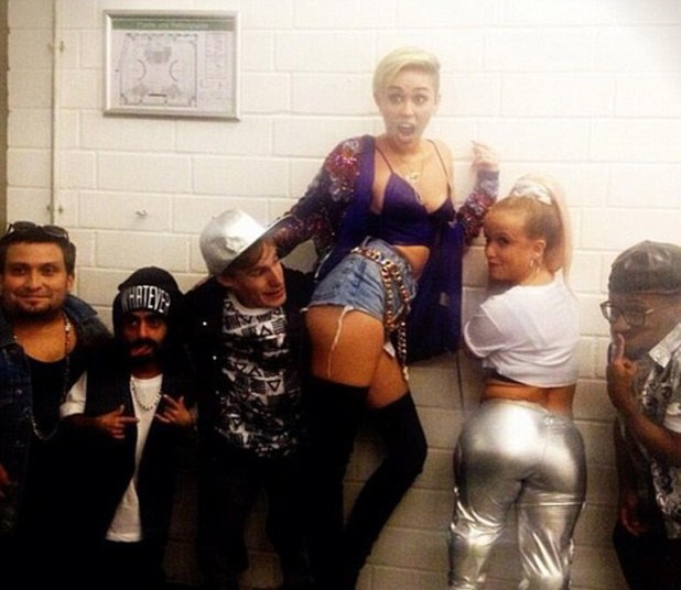 Miley Cyrus poses with her dwarf backing group