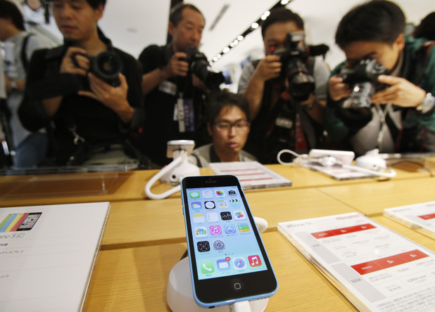 Photographers take pictures of Apple's new iPhones on display at a store in Tokyo