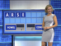 The co-presenter giggles as she places the letters on the board.