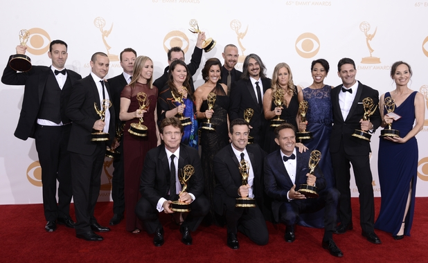 "Mark Burnett, kneeling right, and Carson Daly, kneeling center, and the crew of ""The Voice"" pose backstage with the award for outstanding reality-competition program at the 65th Primetime Emmy Awards"