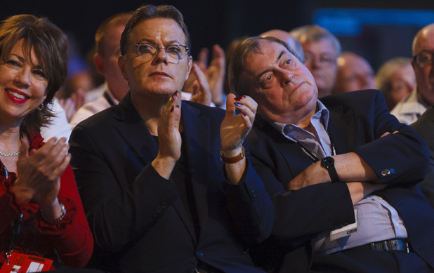 Eddie Izzard and Lord Prescott listen to Ed Miliband during his speech at the Labour Party annual conference at The Brighton Centre