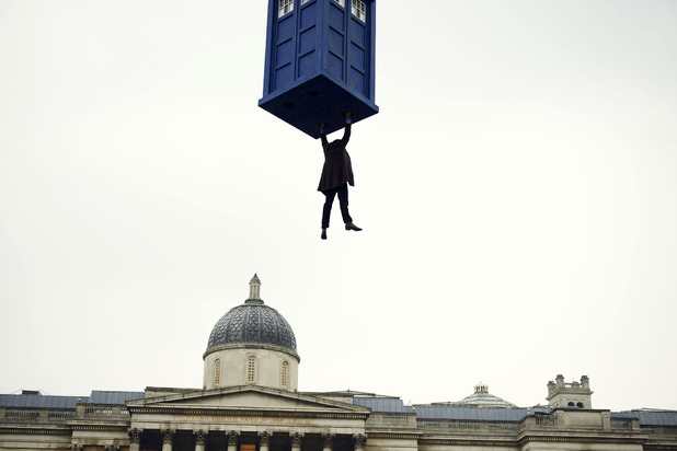 The Doctor dangles from the TARDIS.