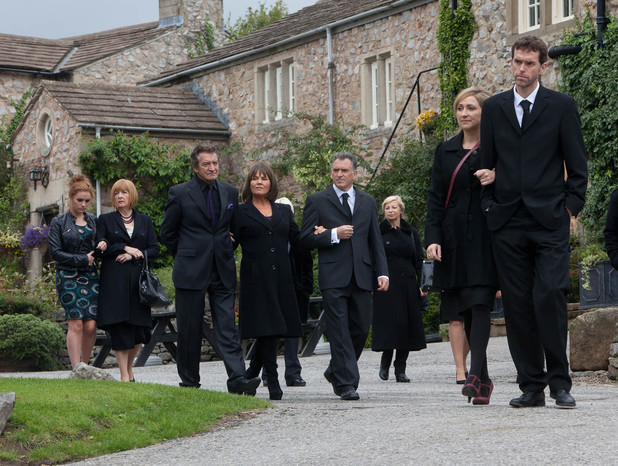 The villagers gather for Alan's funeral.