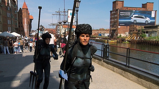 Kim and Nicole pose as a statue of Neptune in The Amazing Race: 'Get Our Groove On'