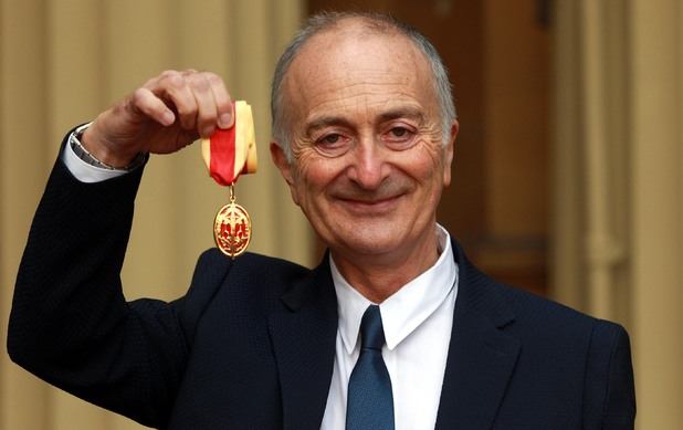 Sir Tony Robinson holds his medal after being knighted by the Duke of Cambridge