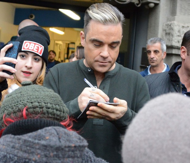 Robbie Williams signs autographs for fans as he leaves Hotel Principe di Savoiato