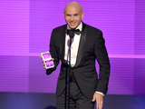 Host Pitbull presents the award for artist of the year at the American Music Awards