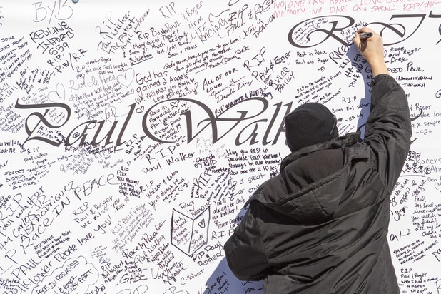 A fan writes messages on a giant poster during a memorial rally for Paul Walker