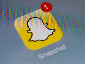 The logo of mobile app 'Snapchat' is displayed on a tablet on