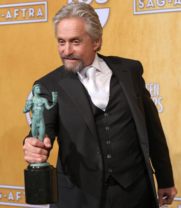 Michael Douglas poses in the press room with the award for outstanding performance by a male actor in a television movie or miniseries for Behind the Candelabra