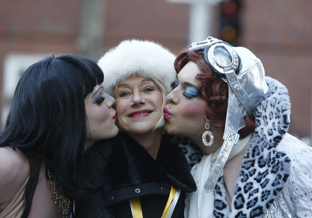 Helen Mirren at the 2014 Hasty Pudding Woman of the Year event is kissed by Harvard University theatrical students as they ride in the back of a convertible during a parade through Harvard Square