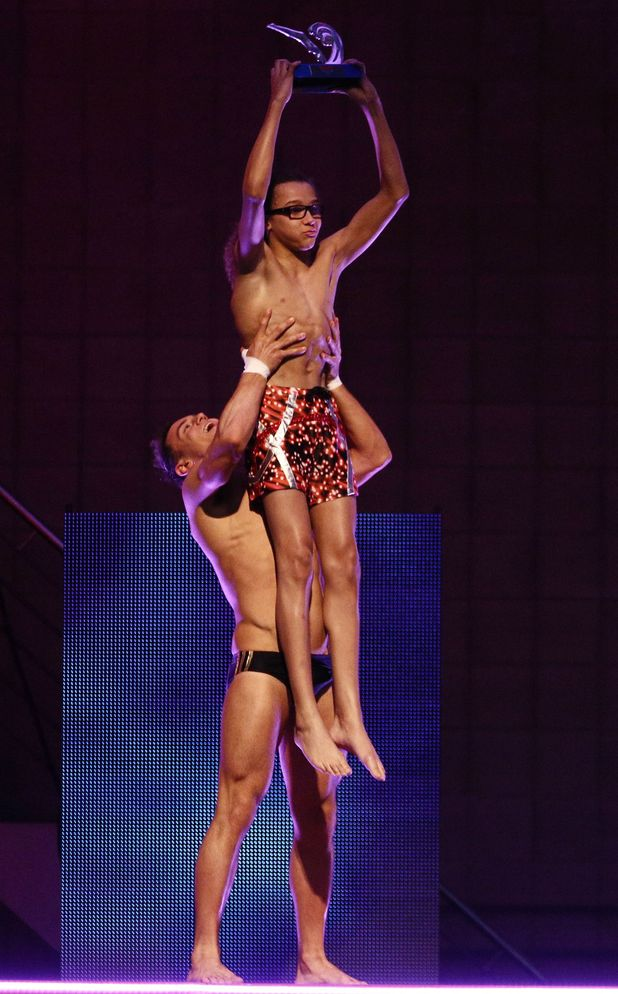 Tom lifts Perri in the air