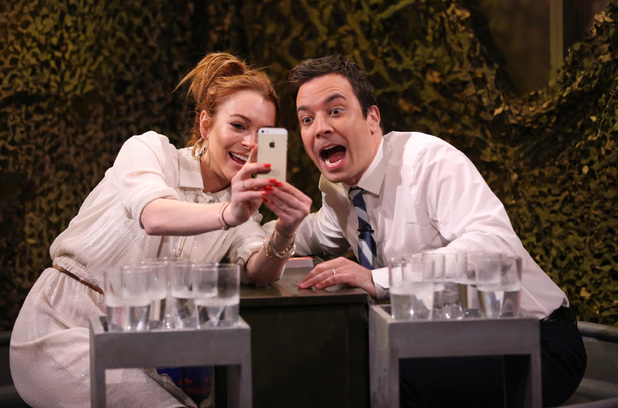 THE TONIGHT SHOW STARRING JIMMY FALLON -- Episode 0014 -- Pictured: (l:r) Lindsay Lohan and Jimmy Fallon play Water War on March 6, 2014 -- (Photo by: Lloyd Bishop/NBC/NBCU Photo Bank via Getty Images)
