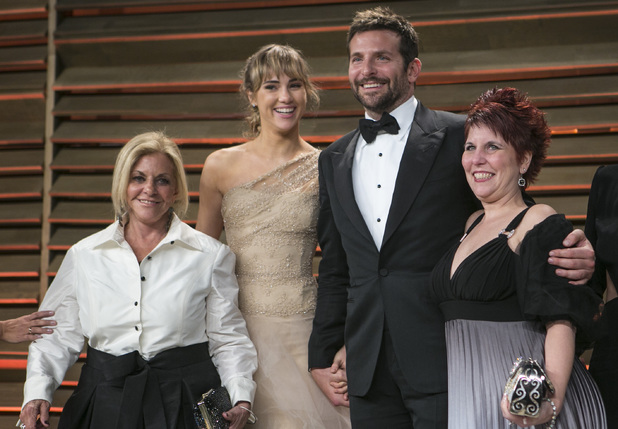 Bradley Cooper, center, and his family arrive to the 2014 Vanity Fair Oscar Party on March 2, 2014 in West Hollywood, California. AFP PHOTO/ADRIAN SANCHEZ-GONZALEZ (Photo credit should read ADRIAN SANCHEZ-GONZALEZ/AFP/Getty Images)