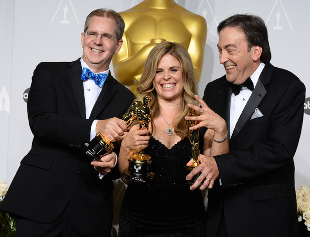 "Chris Buck, from left, Jennifer Lee and Peter Del Vecho pose in the press room with the award for Best animated feature film of the year for ""Frozen"" during the Oscars"