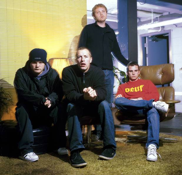 UNITED STATES - FEBRUARY 10: Photo of Jonny BUCKLAND and COLDPLAY and Chris MARTIN and Guy BERRYMAN and Will CHAMPION; L-R: Will Champion, Chris Martin, Jonny Buckland (standing), Guy Berryman - posed, group shot (Photo by Mick Hutson/Redferns)