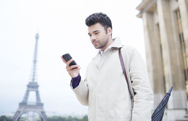 Businessman using phone by Eiffel Tower in Paris