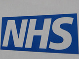 The NHS logo on a sign outside St Thomas' Hospital