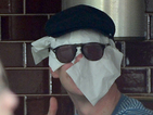 Guess the famous actor hiding behind a makeshift mask of paper napkins.