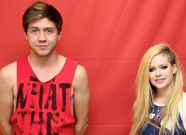 Avril Lavigne poses for an awkward photo with a fan