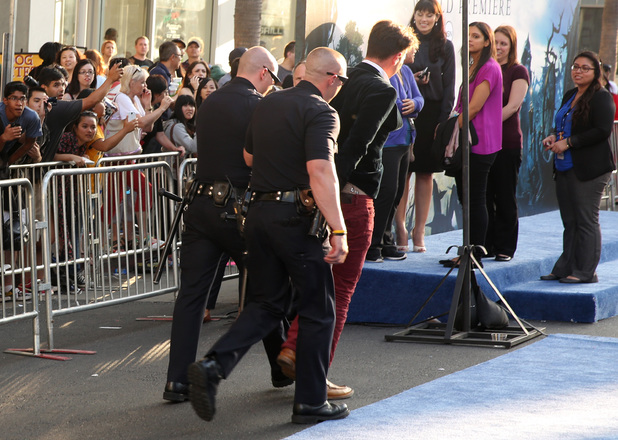notorious red carpet prankster Vitalii Sediuk being led away from the Maleficent premiere