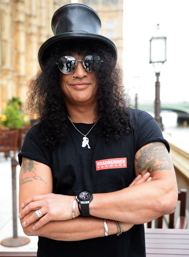 Slash poses outside The Houses of Parliament for the album launch of 'World on Fire'