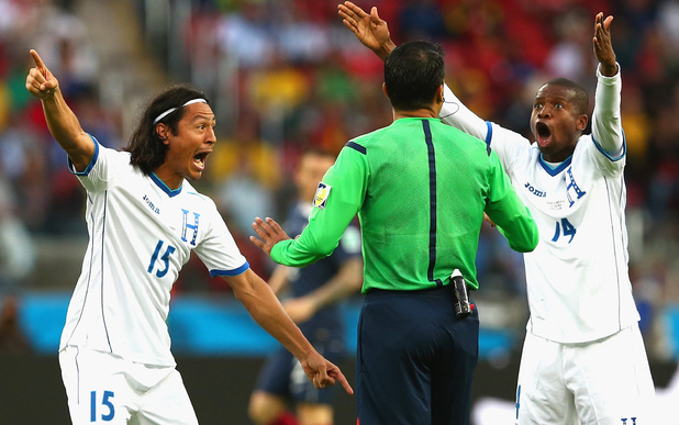 Roger Espinoza and Oscar Boniek Garcia of Honduras protest France's second goal with referee Sandro Ricci during the 2014 World Cup match between France and Honduras