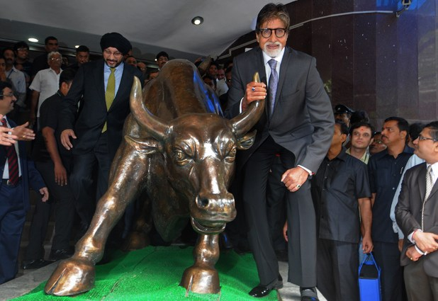 Amitabh Bachchan poses with the bronze bull statue at the Bombay Stock Exchange